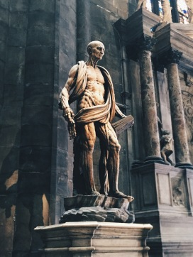 Bartholomew was skinned alive, the statue depicts him skinless and draped in a cloak of his own flayed flesh.